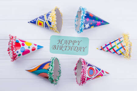 Kids Birthday composition on wooden background. Set of colorful party hats with greeting card in the middle. Holiday decor for Birthday.