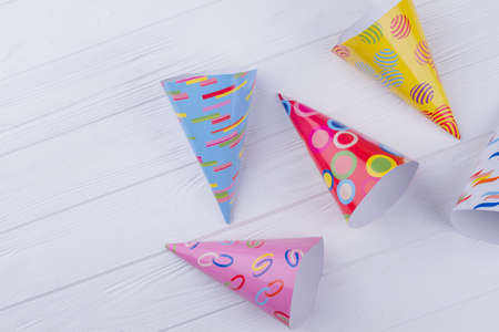 Group of party hats, top view. Decorated Birthday party caps over white background. Paper craft for kids.