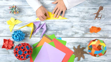Torning yellow paper by hands. Folding colorful paper while making origami figures. Top view, flat lay.