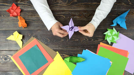Mans hands doing origami flower. Man made purple lily from paper. Japanese craft workshop. Beautiful hobby and activity.