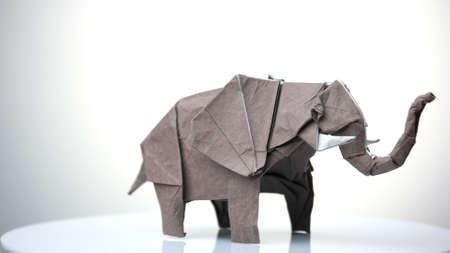 Grey origami elephant. Origami figure exhibition. White isolated background.