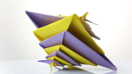 Abstract origami model. Modular 3D figurine made of yellow and violet units. Japanese art of folding paper. Banque d'images