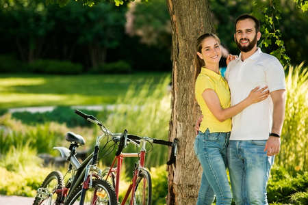 Couple with bicycles in the park. Couple of students in love posing on summer nature background. Romantic travel together.