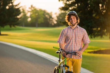 Handsome cyclist on summer vacation. Joyful male student resting with bicycle outdoors and looking at camera. Enjoying summer holidays. Imagens