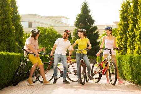 Gruppo di persone gioiose con le biciclette fuori. Quattro amici allegri che trascorrono del tempo insieme all'aperto. Fine settimana dei migliori amici.
