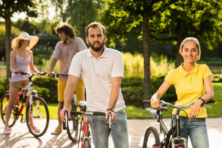 Young students with bicycles outdoors. Smiling tourists with bicycles at summer park. People, tourism and active lifestyle.