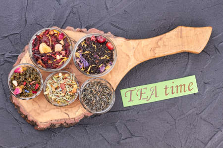 TEA time concept. Rustic wooden board with collection of dried teas on black stone. Ingredients for aromatic drink.