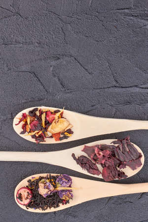 Spoons with dried tea, copy space. Various kinds of tea in spoons on dark slate background. Tea is elixir of life.