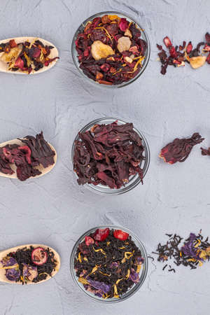 Composition with assorted dried tea leaves. Glass bowls with various dry teas on light background, top view.