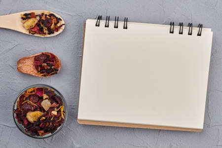 Composition with dried tea on gray background. Fruit tea and blank paper notepad. Imagens