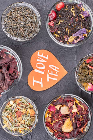 Background of dried tea leaves in bowls. Assortment of dry healthy teas and heart-shaped paper card with inscription I love tea.