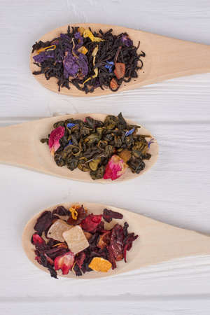 Assortment of dry tea in wooden spoons. Black, herbal and red tea leaves in spoons on white wooden background.