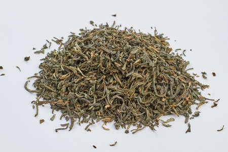 Close up heap of dried green tea leaves. Dry green tea leaves on white background.