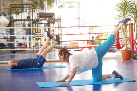 Mature woman doing Pilates exercise. Fit cheerful old woman is doing balanced exercise at gym. Secret of good health of seniors. Stock Photo