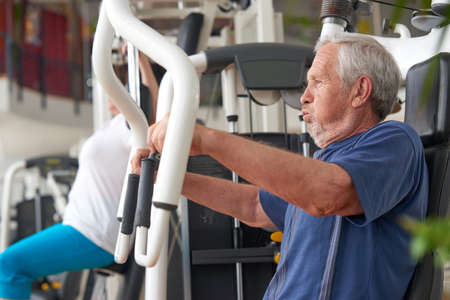 Elderly man doing press push weight exercise. Male person doing hard workout on fitness machine at gym. Healthy body through efforts. Stock Photo