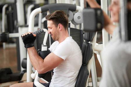 Handsome muscular man in gym doing exercises. Caucasian male taking efforts to finish set on chest press. Regular sport training for perfect shape. Stock Photo