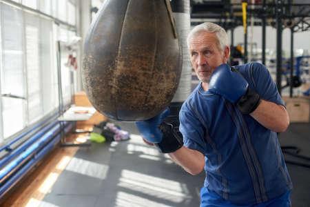 Elderly man hitting punching bag in boxing studio. Senior caucasian man in gloves beats punching bag in gym. Imagens