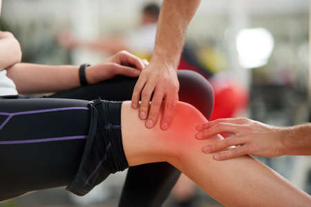 Muscle cramp during workout. Male hands helping relieve pain in female injured leg. Sport accident concept.