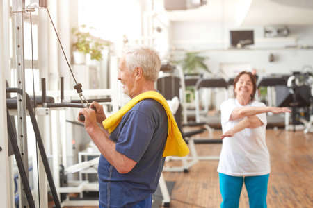 Elderly man working out at fitness center. Side view senior caucasian man with towel on his shoulder training at fitness gym. Sport for all ages.