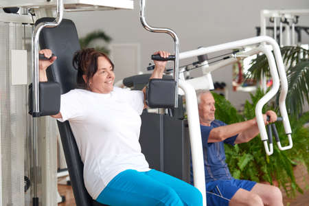 Smiling older woman working out at gym. Pretty positive woman flexing muscles using machine at fitness center. Fitness, sport, training, people and lifestyle concept.