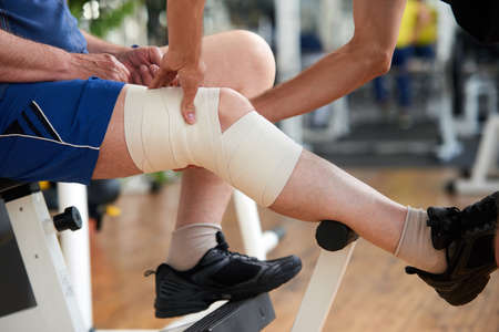 Wrapping knee injury. Male hands fixed elastic bandage on mans injured leg at gym. Muscle strain concept.