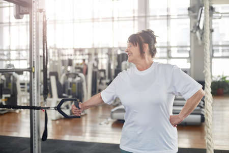 Elderly woman training hand at gym. Suspension training for older adults.