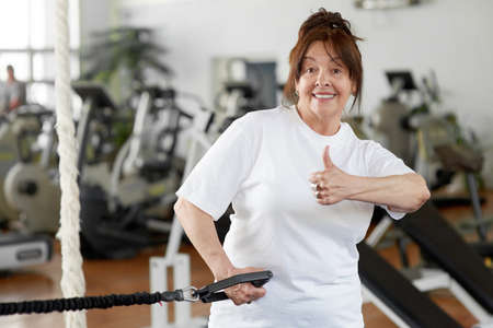 Elderly woman in gym showing thumb up. Happy senior woman looking at camera at fitness club. People, sport, gestures, healthy lifestyle.