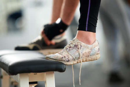 Female feet in sneakers in gym close up. Cropped image of womans leg in running shoes with untied laces at fitness club. People, fitness, active lifestyle concept. Stock Photo
