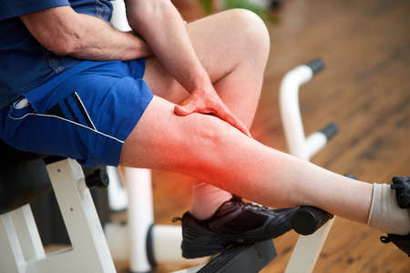 Senior man with knee pain at gym. Elderly man massaging his knee at fitness club. Trauma during workout.