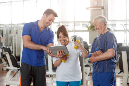 Personal trainer giving instructions to elderly couple in gym. Elderly woman discussing workout progress with fitness instructor. Sport, fitness, technology and people concept.