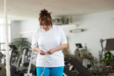 Senior woman with measuring tape at gym. Older caucasian woman measuring her waist by tape measure at fitness club. Sport for weight loss.