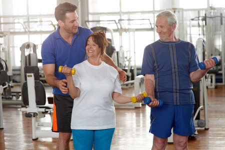 Knappe mannelijke trainer die hogere vrouw instrueert in gymnastiek. Ouderen trainen in de fitnessclub. Sport, recreatie, gezonde levensstijl.