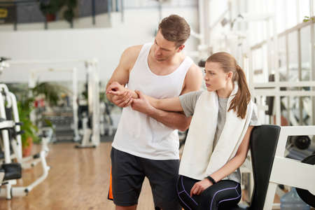 Woman with joint pain in gym. Young muscular trainer touching female injured hand at fitness club. Sprained wrist injury. Exercises for wrist strain.