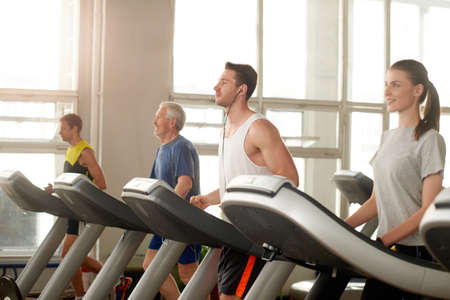 Group of people on treadmill at gym. Handsome young man running on treadmill. Exercise at the fitness club.