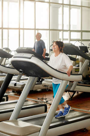 Smiling senior woman running on treadmill in gym. Cheerful aged woman in sportswear using treadmill machine at fitness center. People, fitness, active way of life.
