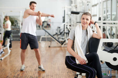 Portrait of tired woman having rest after workout. Beautiful sporty girl with towel and sweat looking at camera at modern gym. Handsome muscular man working out on the background.