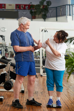 Senior couple giving thumbs up at gym. Happy woman smiling on weighing scales at gym. People, sport, fitness, diet and weight loss concept.