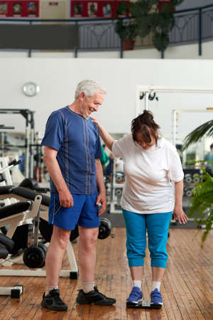 Senior woman stands on weight scale at gym. Happy elderly couple at fitness club. Checking weight loss result.