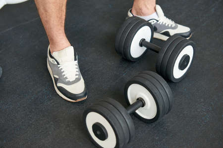 Sportsman in sneakers standing with dumbbells on the floor. Cropped image of male legs in sportswear with dumbbells at gym. Sport fitness theme.