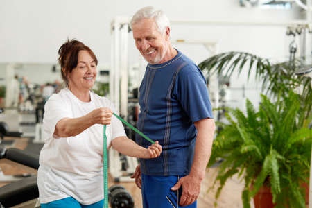 Beautiful elderly couple at sport club. Happy senior lady with measuring tape showing her fitness results at fitness club. People, sport, diet and weight loss concept. Imagens