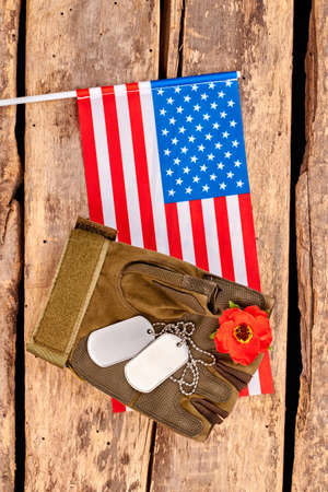 US army soldier essentials and flag. Close up, top view. Wooden desk surface background.