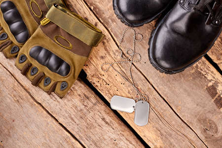 Military soldier accessories. Gloves, dog tags and boots. Flat lay, top view.