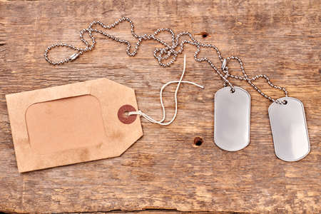 Military dog tags close up. Wooden background.