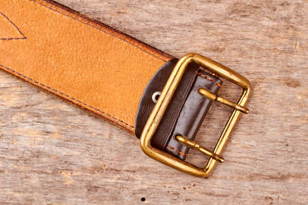 Golden leather belt. Soldiers belt on wood, top view, flat lay.