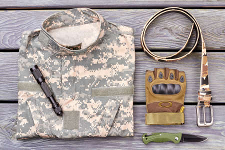 Military jacket and accessories. Torch, glove, belt and knife on wood.