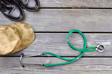 Military medical equipment. Top view, flat lay. Green stethoscope, cap and combat boots.