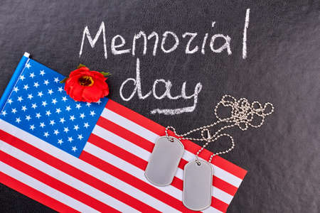 American memorial day flat lay. Usa flag, dog tags and red poppy, top view. Black leather background.