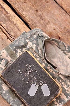 In memory of a brave soldier. Military camouflage clothes, old book, and dog tags on wood. Stock Photo