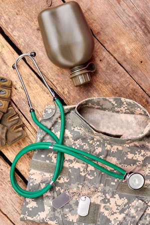 Military outfit and accessories, flat lay. Top view, stethoscope, clothes, bottle, gloves and dog tags. Wooden background.