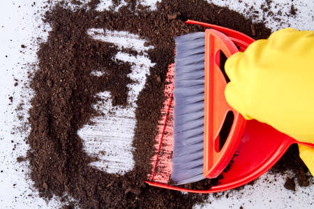 Soil, dustpan and broom close up. Close up of person wearing gloves sweeping floor with broom and dustpan. Reklamní fotografie
